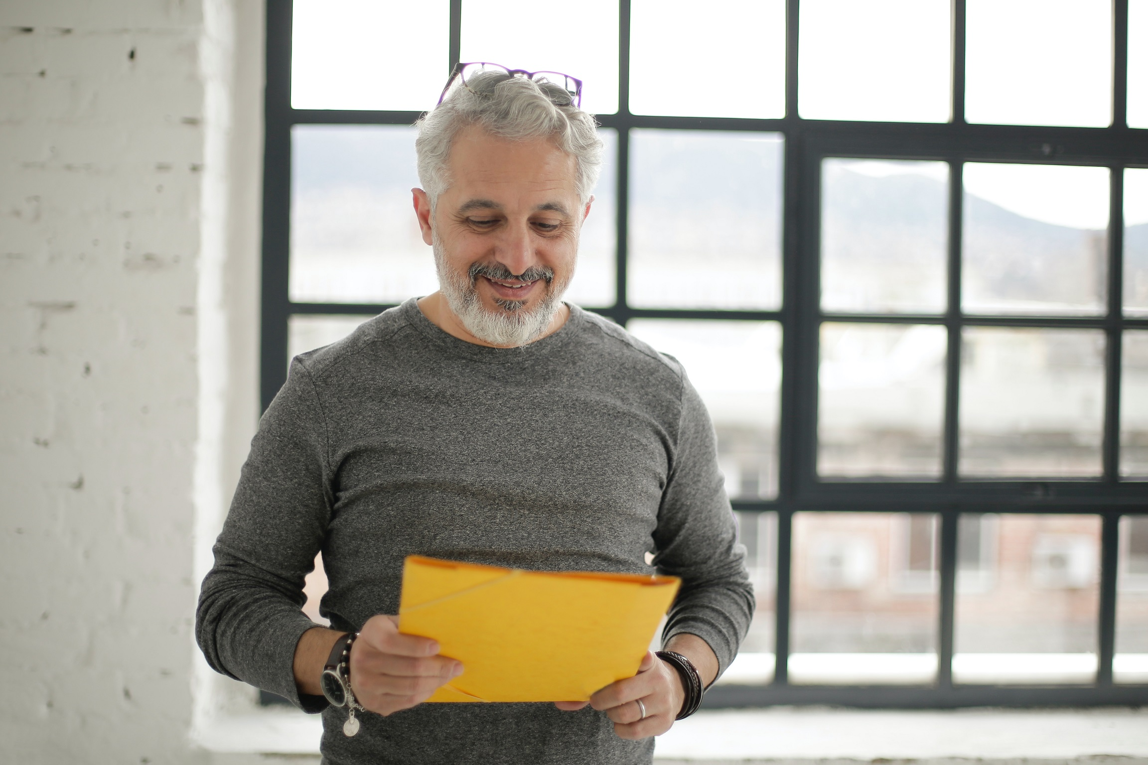 cheerful-mature-male-employee-holding-documents-against-3931608